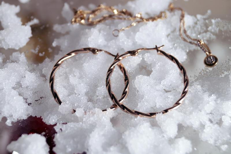 Gold jewelry beauty accessories women lie on white snow stock photography