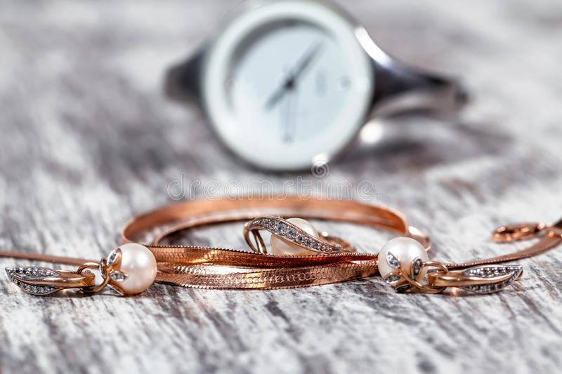 Gold jewelry with pearls and elegant women`s watches stock images