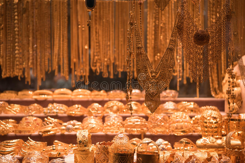 Gold jewelry in the shop window. Fashion jewelry from yellow and white gold, on a window shop stock images