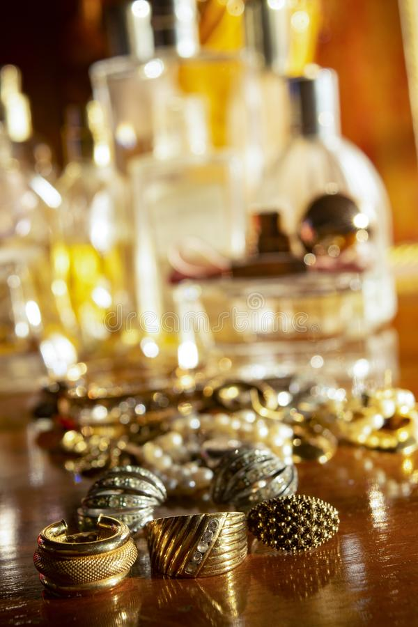 Gold jewels on a wooden plane. Gold family jewels on a wooden chest of drawers stock photography