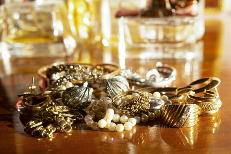 Gold jewels on a wooden plane. Gold family jewels on a wooden chest of drawers stock image