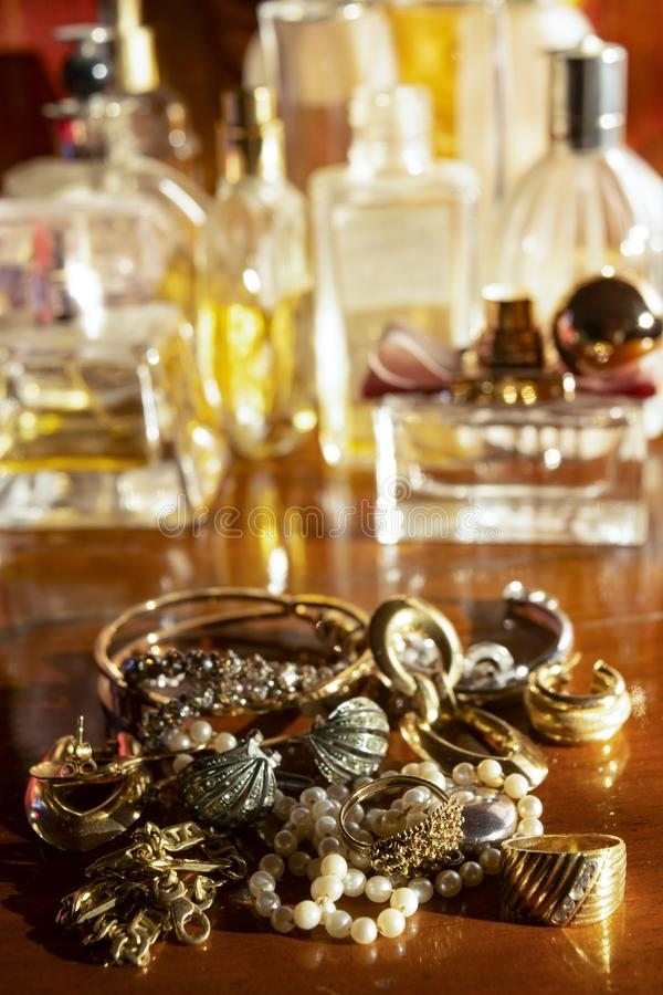 Gold jewels on a wooden plane. Gold family jewels on a wooden chest of drawers stock photos