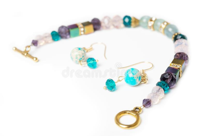 gold jewerly braslete with semiprecious and cristal at white background stock photo