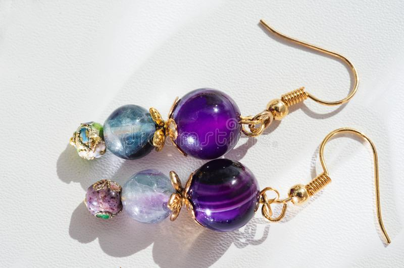 gold jewerly earrings with agat and fluorite semiprecious at white background stock image