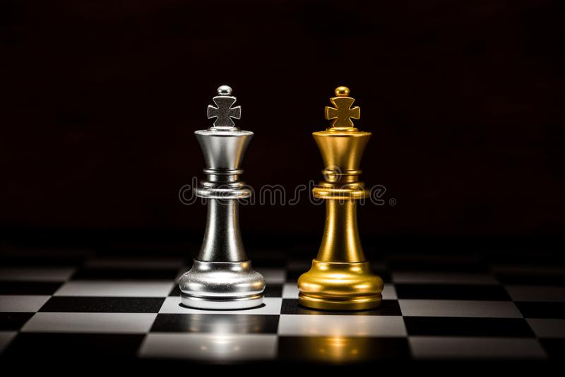 Gold king chess facing silver king chess on chess board , business strategy concept.  stock photo