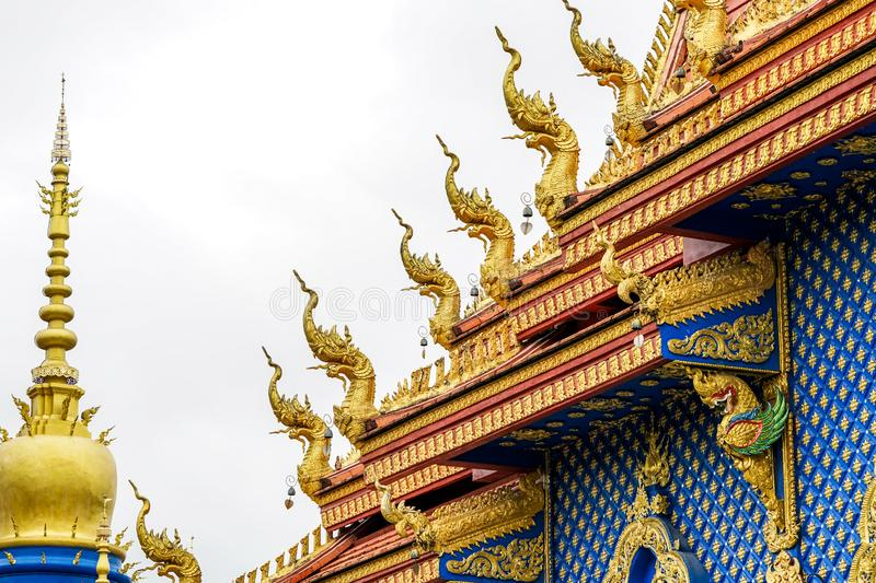 Gold king of snake statue on the temple rooftop. Beautiful gold statue King of snake on the top of Thai temple. In Buddhist tales, It wanted to be a monk but it royalty free stock images