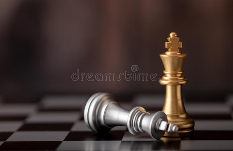 Gold king standing and silver falling on chess board. With wooden background, battle, bishop, business, castle, challenge, checkmate, chessboard, choose stock photography