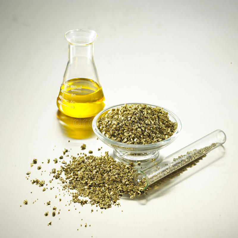 Gold in laboratory glass stock images