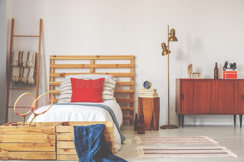 Gold lamp between wooden cabinet and bed with red cushion in sport bedroom interior. Real photo. Concept stock photos