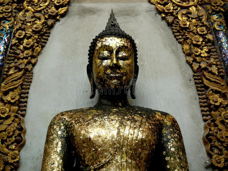 Gold Leaf Buddha in Shrine. A shrine with a Buddha covered in golden leafs.  The golden leaf is to honor the Buddha teachings stock image