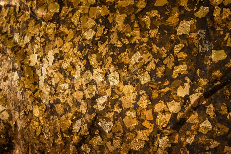 Gold leaf on the wall concrete surface background. Shiny yellow leaf with scraps of gold foil texture background and empty space stock photography