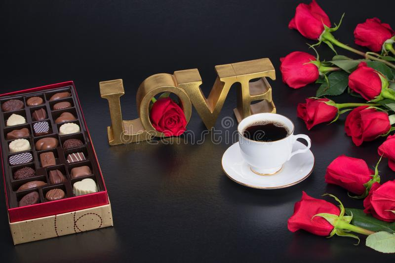 Best valentines presents, red roses and a box of chocolate candy next to a good cup of coffee stock images