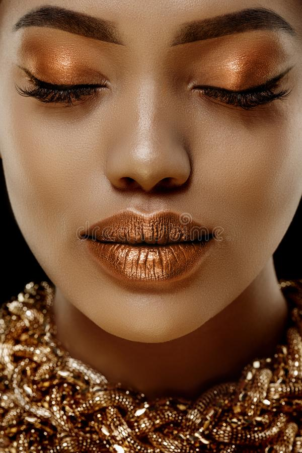 Gold Luxury black skin woman African Ethnic female face. Young african american model with jewelry.  royalty free stock image