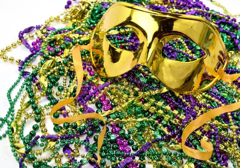 Gold Mardi Gras Masquerade Mask. On background of Mardi Gras beads stock image
