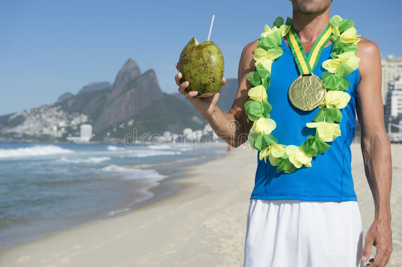 Gold Medal Athlete Celebrating with Coconut Rio. Gold medal athlete celebrating winning with coconut on Ipanema Beach Rio de Janeiro Brazil royalty free stock photography