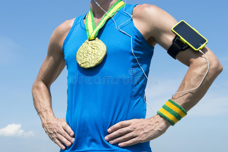 Gold Medal Athlete with Mobile Phone Armband. Gold medal athlete standing with mobile phone armband and headphones against blue sky stock photography