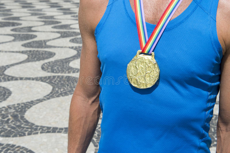 Gold Medal Athlete Rainbow Ribbon Rio. Gold medal first place athlete standing with gay pride rainbow ribbon at the Copacabana Beach sidewalk in Rio de Janeiro royalty free stock images