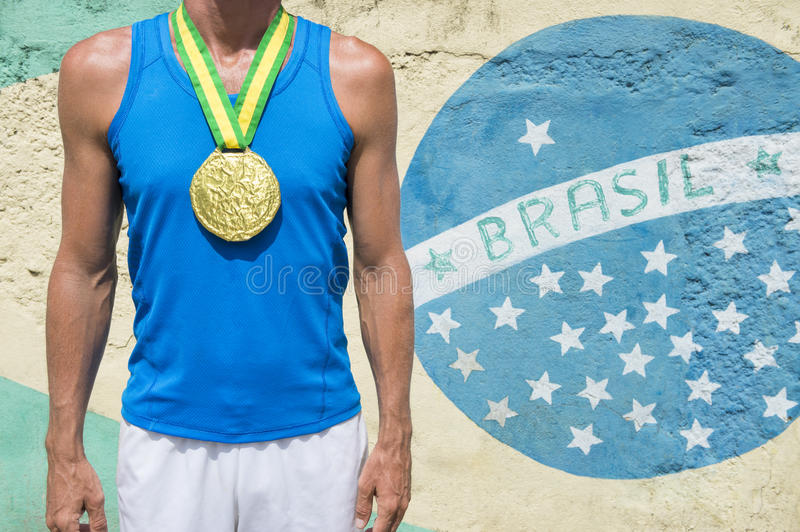 Gold Medal Athlete Standing Brazilian Flag Rio. Brazil champion first place athlete wearing a gold medal standing in front of a Brazilian flag mural Rio de stock image