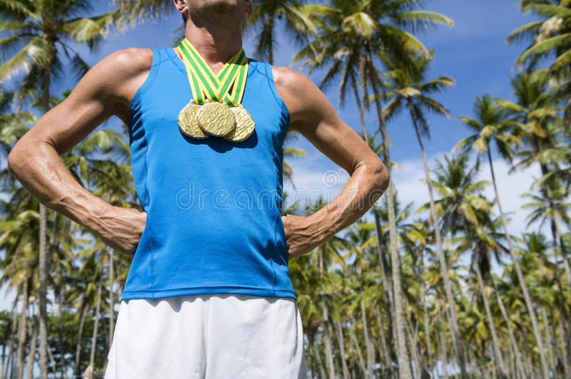 Gold Medal Athlete Standing with Palm Trees Brazil. First place athlete wearing gold medals standing outdoors with hands on hips in grove of tropical palm trees stock photo