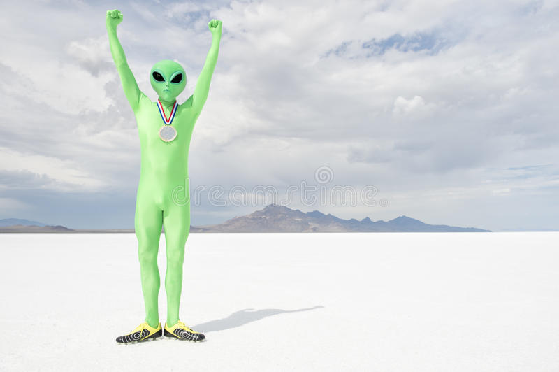 Gold Medal Green Alien Standing on White Planet. Green alien athlete wearing gold medal standing with arms raised on stark white planet background stock photography