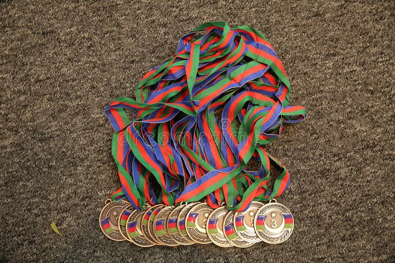 Gold, medal with numbers Three. Sport trophy. Blue background. Gold medal on black background stock image