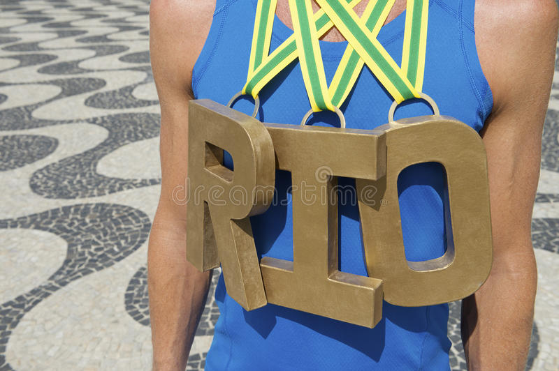 Gold Medal RIO Olympic Athlete Standing Copacabana Beach. RIO first place athlete wearing gold medals standing outdoors on Copacabana Beach Rio de Janeiro Brazil royalty free stock photo