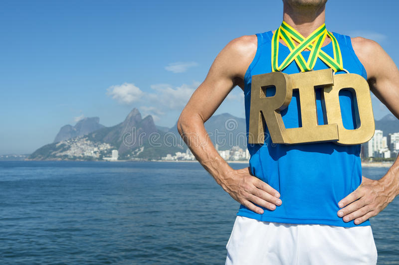 Gold Medal RIO Olympic Athlete Standing Ipanema Beach. RIO 2016 first place athlete wearing gold medals standing outdoors in front of the sea at Ipanema Beach stock image