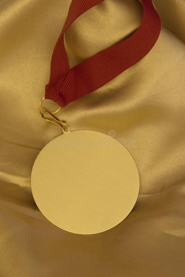 Gold medal on shiny golden cloth royalty free stock photos
