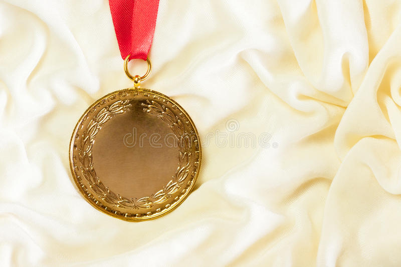 Gold Medal on Silk. A rugged gold medal setup majestically against a cream colored silk cloth stock image