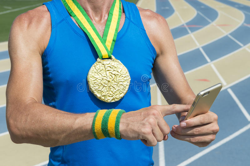 Gold Medal Track Athlete Using Mobile Phone. Gold medal athlete standing at running track using his mobile phone stock photos