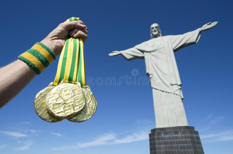 Gold Medals Christ the Redeemer Rio. Hand holds gold medals hanging from Brazil color ribbons in clear blue sky next to the statue of Christ the Redeemer stock image