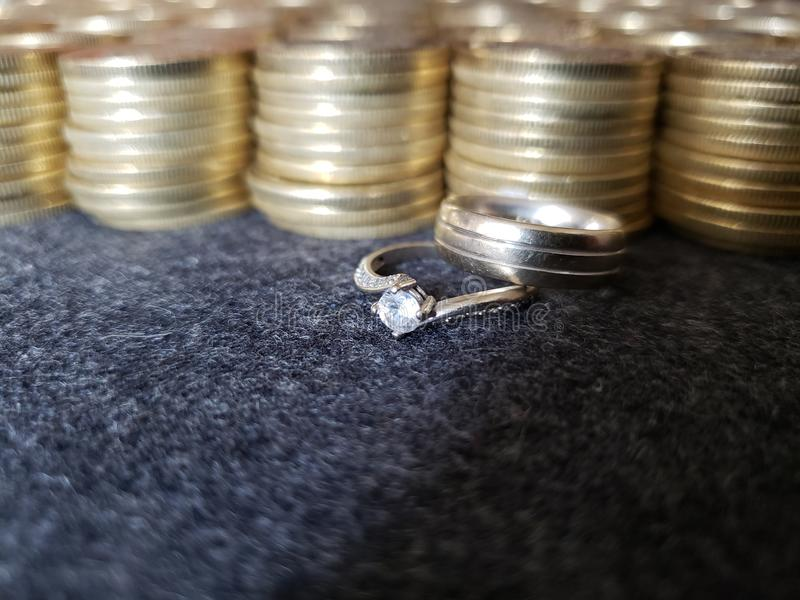 Gold and metal business, engagement ring and marriage with gold coins stacked. Trading and exchange, bank and commerce, price of buy and sell, cash value and stock images