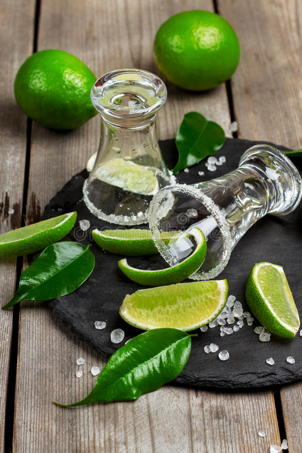 Gold mexican tequila shot. Still life, food and drink, holidays concept. Empty glass of mexican tequila shot with lime and salt on a grunge wooden table royalty free stock image