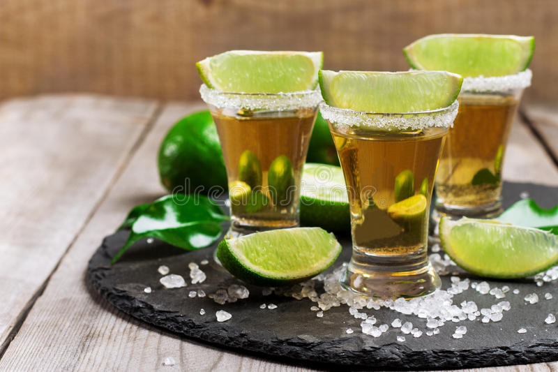 Gold mexican tequila shot. Still life, food and drink, holidays concept. Gold mexican tequila shot with lime and salt on a grunge wooden table. Selective focus royalty free stock image