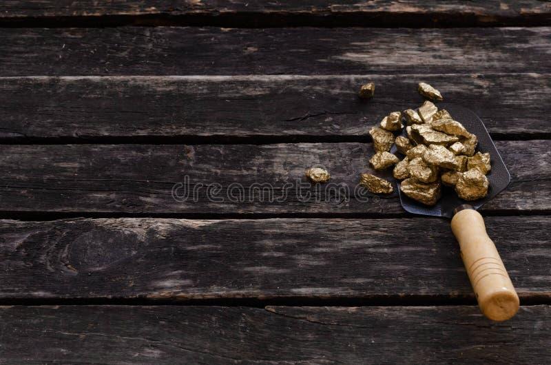 Gold mine. Gold miner. Golden ore in a shovel. Gold ore nuggets in shovel on old adventurer table. Goldminer Treasure hunter concept stock photos