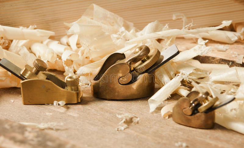 Gold miniature wood planer on wooden plank royalty free stock photo