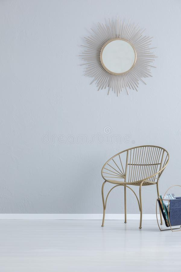 Gold mirror on grey empty wall above armchair in simple hall interior with copy space. Real photo stock images