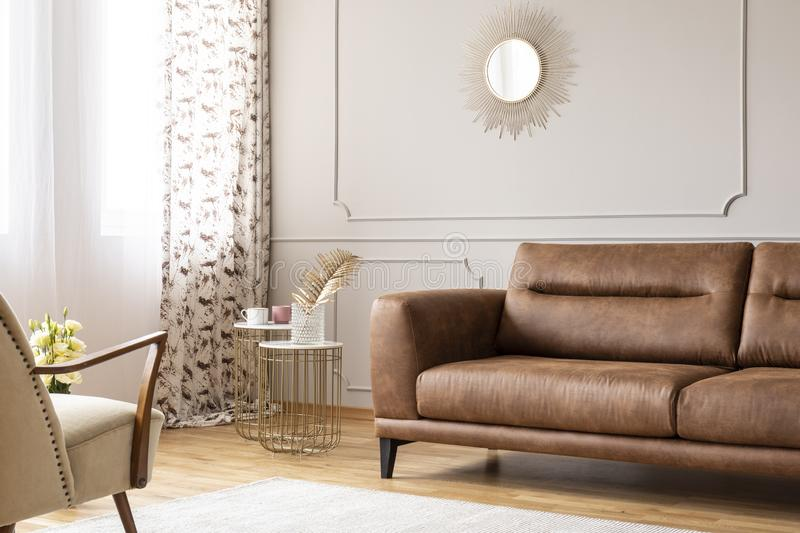 Gold mirror on grey wall with molding above leather settee in flat interior with tables and armchair stock images