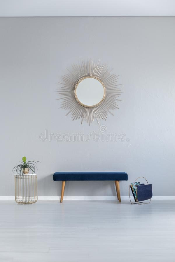 Gold mirror on the wall above blue bench in grey minimal entrance hall interior with table royalty free stock images