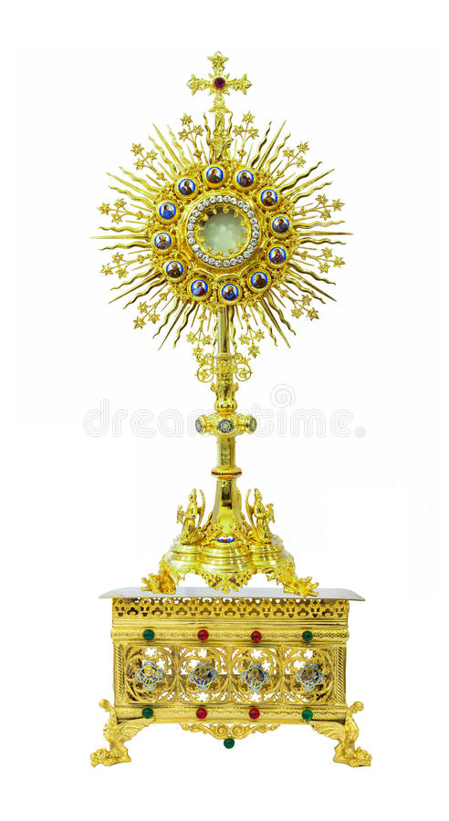 Gold monstrance on the pedestal engraving 4 saints on white back. Antique gold monstrance on the pedestal engraving 4 saints on white background stock photography