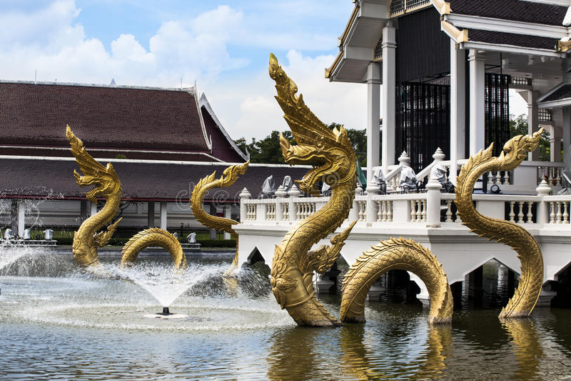 Gold Naga (Dragon, great naga, king of naga, very great snake) with fountain. Naga is the Sanskrit and Pali word for a deity or class of entity or being, taking royalty free stock photography