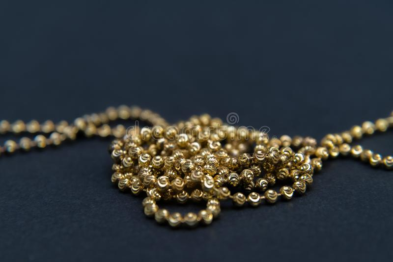 Gold necklace isolated on black background, macro closeup showing yellow golden chain links detail royalty free stock photo