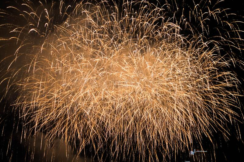 Gold night fireworks on a summer holiday. Many colorful explosion of Fireworks fly night sky in Krasnoyarsk, Russian Federation royalty free stock image