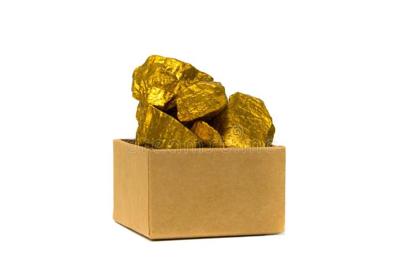 Gold nuggets or gold ore and cardboard box isolated on white background. Gold nuggets, gold ore , precious stone or lump of golden stone and cardboard box royalty free stock photo