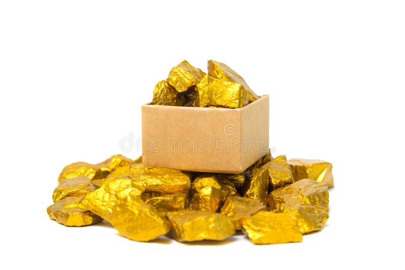Gold nuggets or gold ore and cardboard box isolated on white background. Gold nuggets, gold ore , precious stone or lump of golden stone and cardboard box stock images