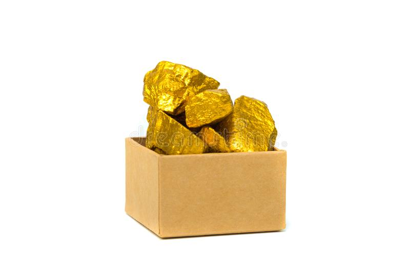 Gold nuggets or gold ore and cardboard box isolated on white background. Gold nuggets, gold ore , precious stone or lump of golden stone and cardboard box royalty free stock images