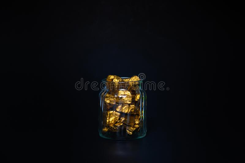 Gold nuggets or gold ore and glass jar in dark room. Gold nuggets, gold ore , precious stone or lump of golden stone and glass jar in dark room stock photo