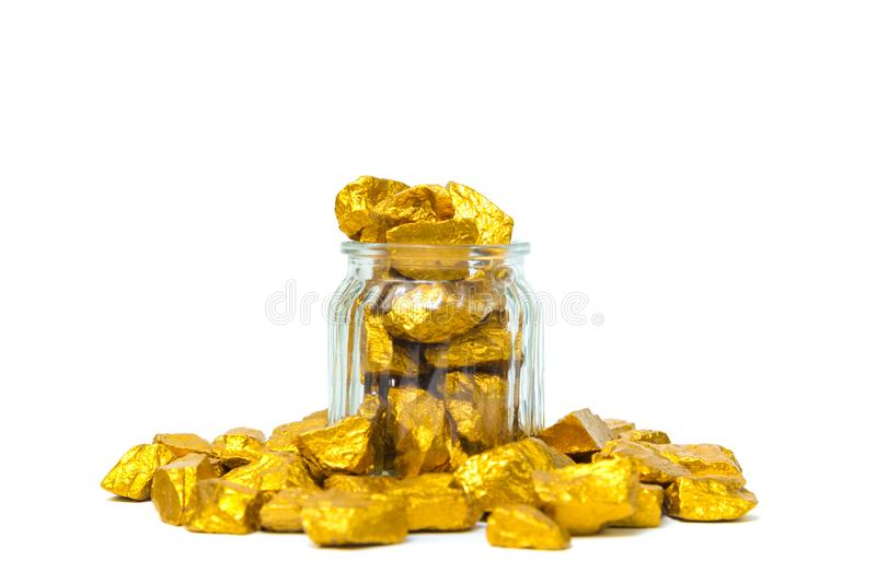 Gold nuggets or gold ore and glass jar isolated on white background. Gold nuggets, gold ore , precious stone or lump of golden stone and glass jar isolated on royalty free stock photography