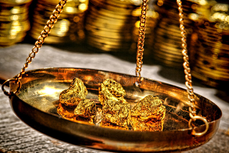 Gold Nuggets in Scale Pan at Precious Metal Dealer. Small gold nuggets being checked for weight old style in an antique measuring scale suspended brass pan at a stock photography