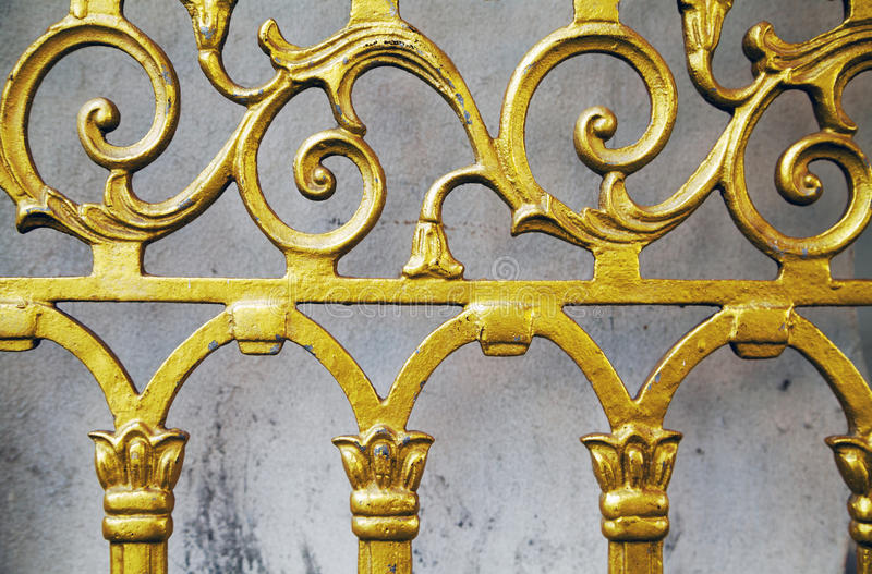 Gold old wrought fence close-up background. Forged ornate beautiful pattern golden gate stock photos